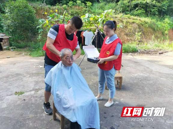 计生协组织志愿者定期上门为计生家庭老人剪头发。.wm.jpg