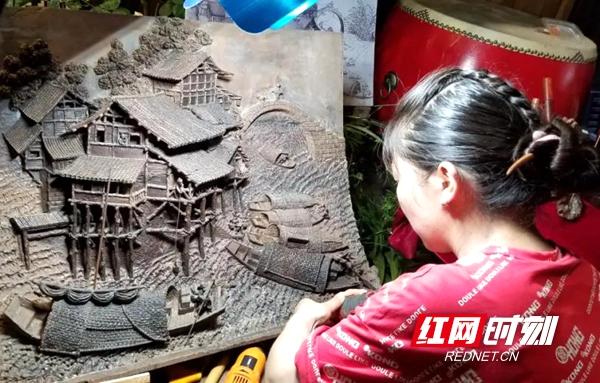麻阳街上的非遗文创集市,潘能辉木雕馆正在现场雕刻文创作品,这些作品让游人穿越到百年前的大小河街。