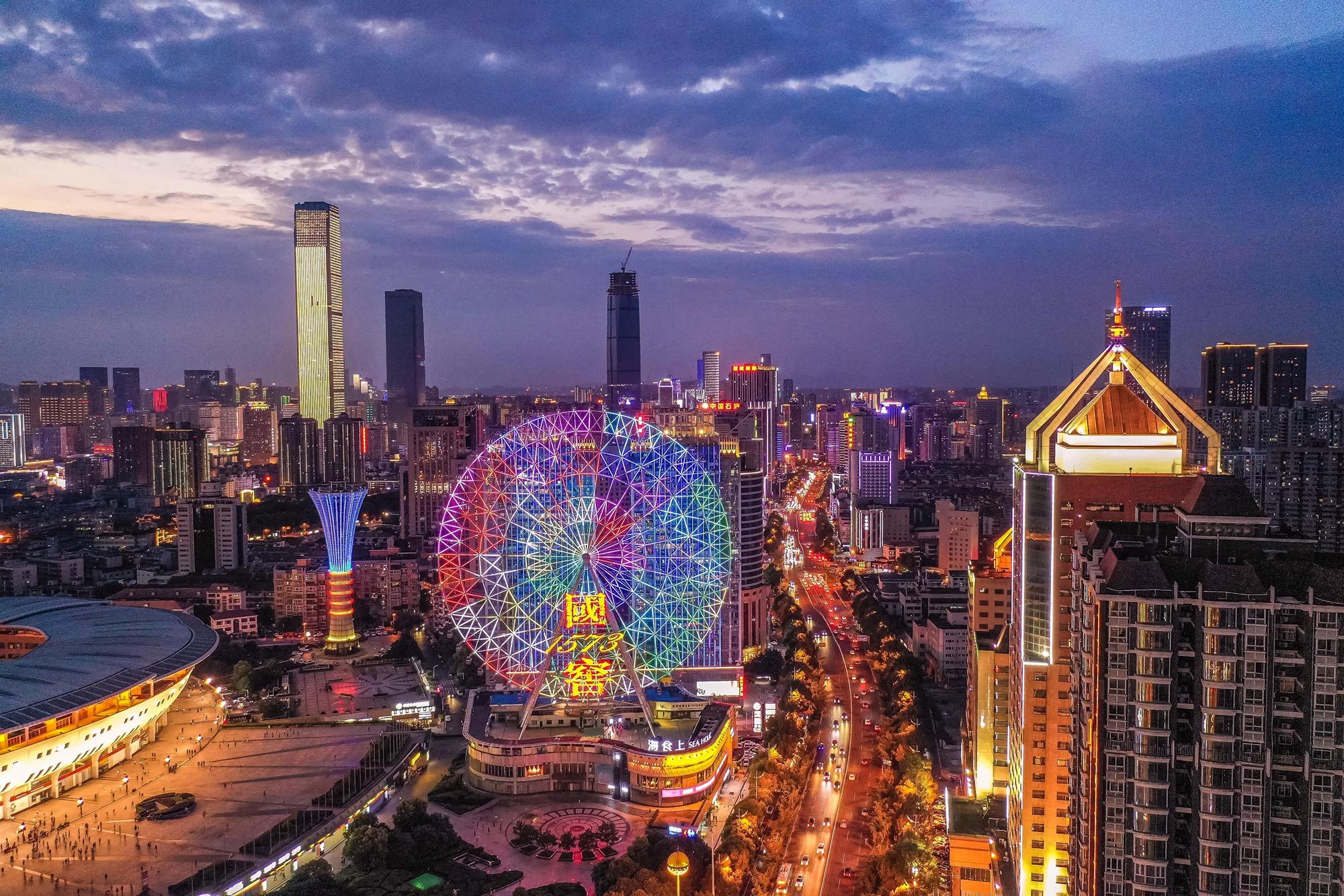 【28号作品:彩色摩天轮】 夜幕降临,贺龙体育广场摩天轮闪烁五彩霓虹,周边高楼鳞次栉比,一片繁华。