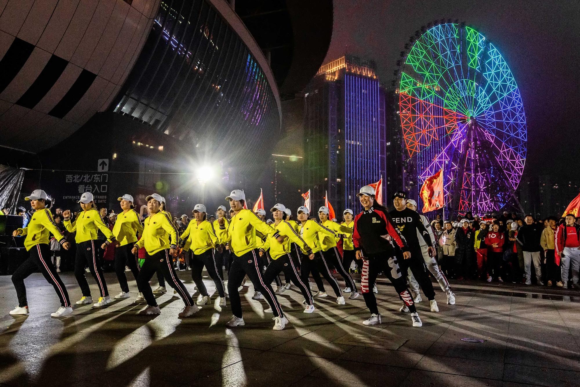 【20号作品:尽情起舞】 夜色灯光下,贺龙体育馆东广场,曳步舞爱好者尽情起舞,激情飞扬。