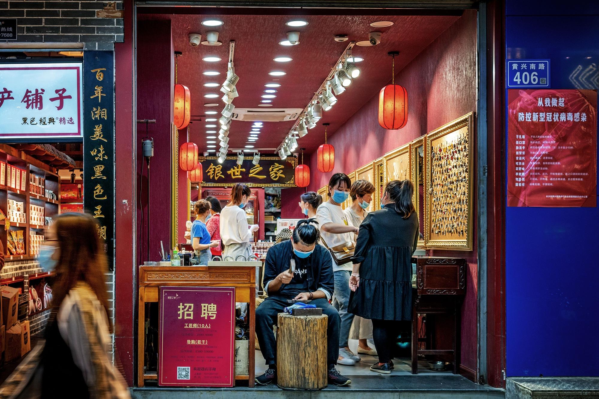 【30号作品:现场打制】 黄兴南路步行商业街不缺传统老手艺,帅气的银匠现场打制银饰品深受美女们青睐。