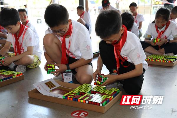 50多名挑战者根据分组,拼出相应的魔方图案,再由各小组的魔方图案一起拼成一幅大型魔方图案,用时1个小时13分钟。