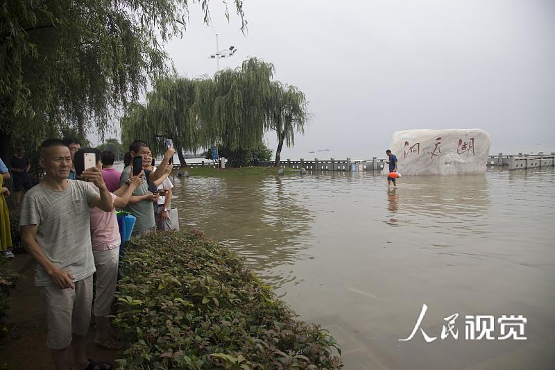 2020年7月30日,湖南岳阳,岳阳市洞庭湖南岳坡码头附近水域,市民争相来看大水。