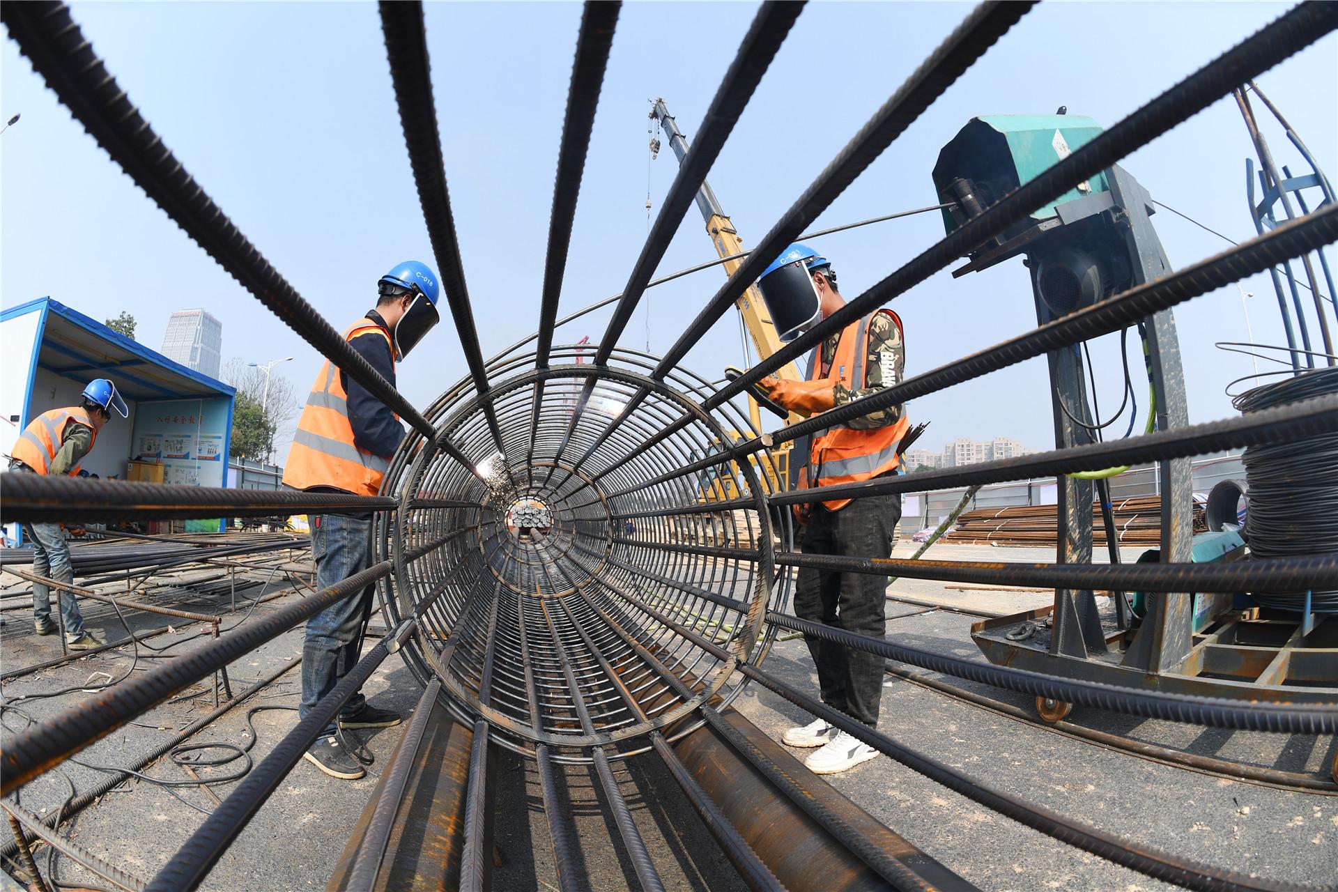 2021年2月23日,长沙市轨道交通1号线北延一期工程青竹湖路站施工现场,施工人员在焊接桩基钢筋笼。