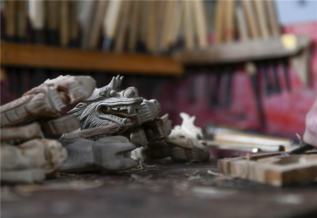 """2021年4月18日,湖南省道县上关街道办事处水南社区,72岁的周承云雕刻的小龙舟""""龙头""""。出生于""""木匠世家""""的周承云,16岁就跟着爷爷、父亲学习木工,主要以手工制作龙舟""""龙头""""为主。近年来,随着旅游产业的兴起,周承云在加工龙舟""""龙头""""的同时,瞄准旅游产业市场,寄情于小龙舟模型的制作。一条小小的龙舟从选底骨、打水平、做大旁、安龙肠、抛光、打漆等多道工艺都是靠手工完成。"""