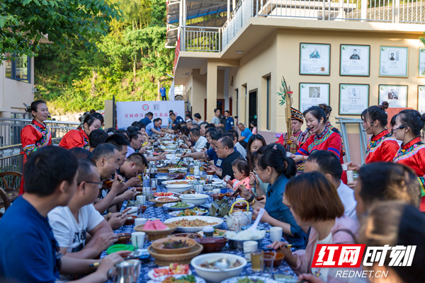 12、长桌宴。宾客们在长桌阵里一字排开、相对而坐,锅巴肉、山鸡肉、野菜……丰富的菜品让人大快朵颐,无论是舜皇山当地老乡还是远到而来的贵宾,大家都沉浸在节庆的喜悦之中。.jpg