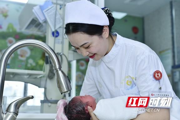 """长沙市妇幼保健院产科护士正在手把手演示婴儿沐浴技巧,手法温柔娴熟,宝宝很乖很享受。帮助家长掌握照顾宝宝的方法,让新手父母快速""""上路""""。"""