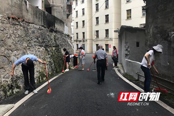 志愿者与居民共同清理道路旁的垃圾和苔藓_副本.jpg