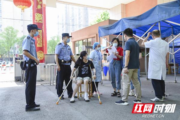 6月7日,高新区公安民警护航行动不便学生进入考场。柯鸣 摄.jpg