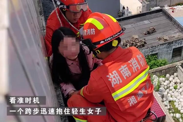 湖南湘乡:不到一米宽的楼顶外缘 消防队员飞身救下女子!