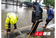 隆回城管系统干部职工冒雨清理道路排水口